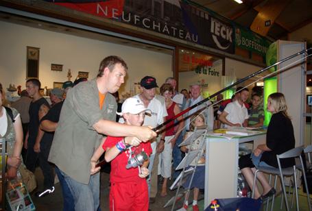 Le président de la MPLux apprend un enfant à pêcher sur le simulateur de pêche