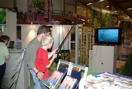 Un membre de la Maison de la pêche luxembourgeoise aide un enfant à pêche grâce au simulateur de pêche